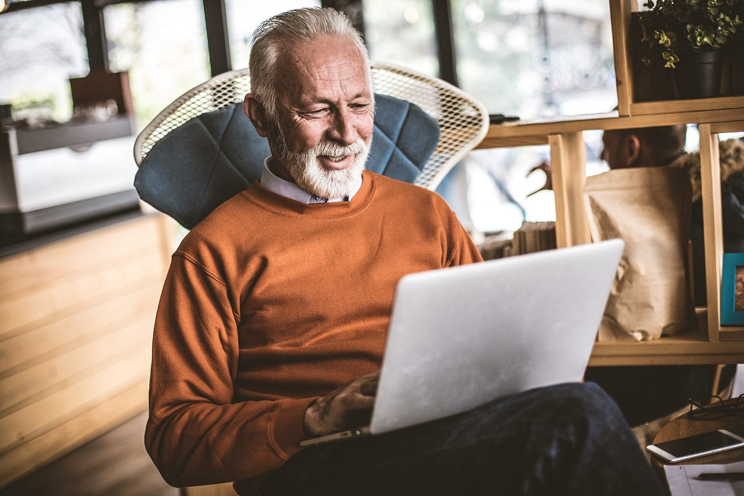 Elder man on computer researching retirement